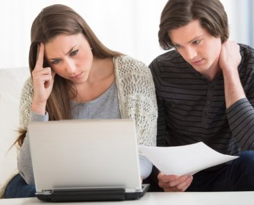 Worried young couple calculating finance on laptop at home