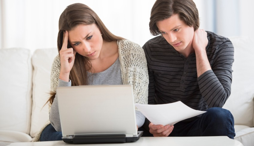 Worried Couple Calculating Finance On Laptop